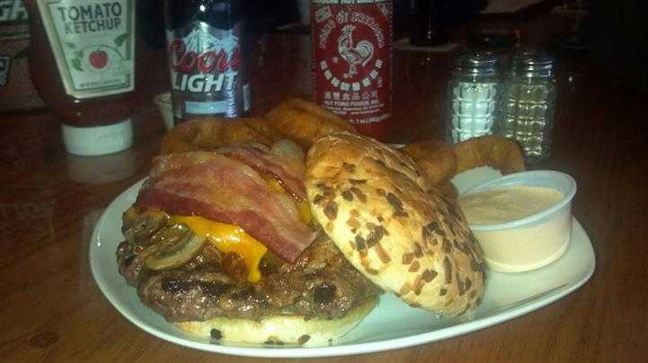 An open faced burger with bacon mushrooms and cheddar, served with onion rings and dipping sauce in front of coors light can and condiments