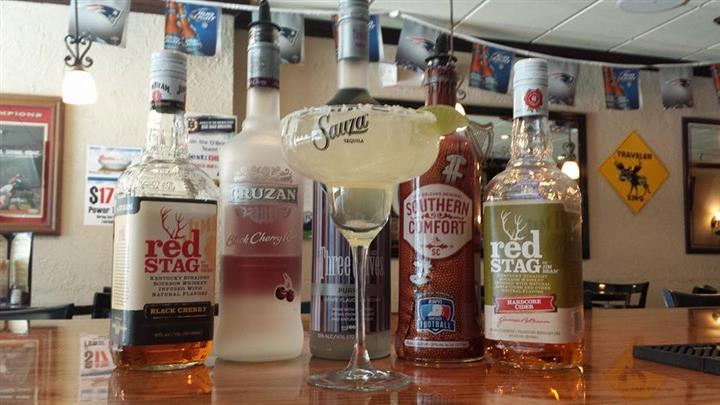 Full margarita in glass in front of bottles of alcohol on bartop