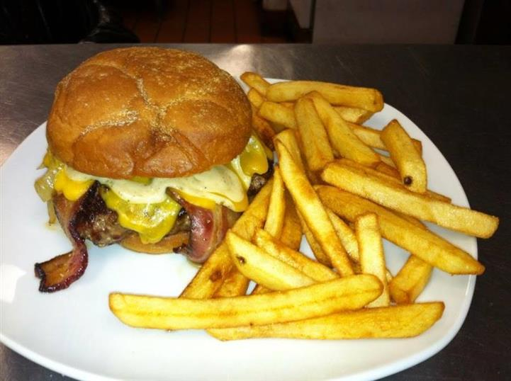 A cheeseburger with bacon served with French fries
