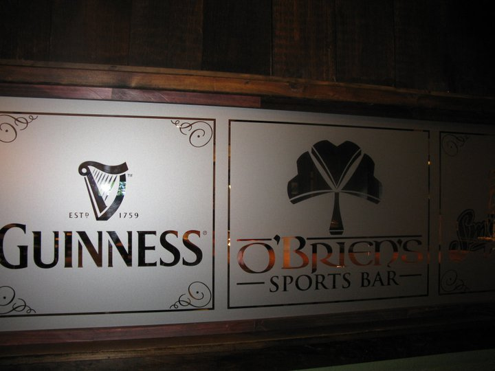 Two smoked glass dividers, one  having Guinness beer trade mark and other with O'Briens sports bar