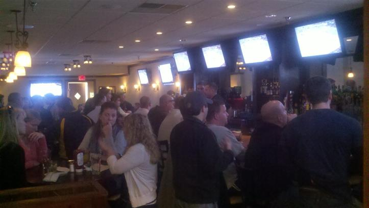 View of bar filled with people watching six TV screens behind bar.