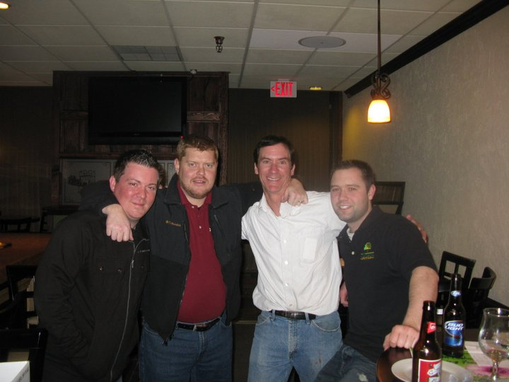 Four men posing for photo with arms around each other