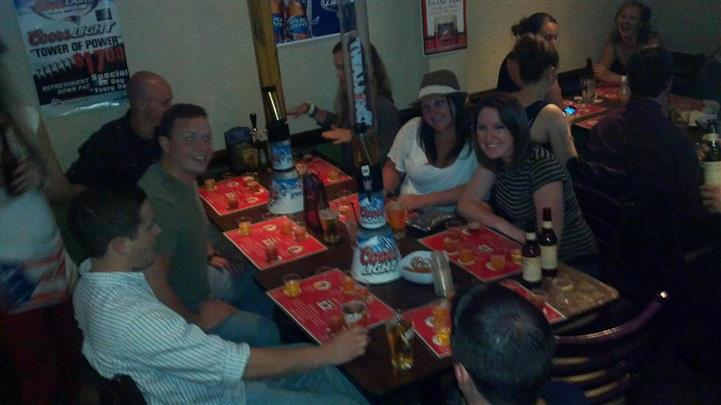 Friends gathered at dining room table with beers and alcohol drinks