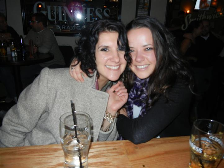 Two women posing for photo leaning in close