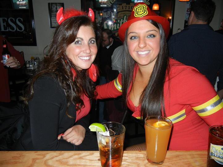 Two women posing for photo in costumes