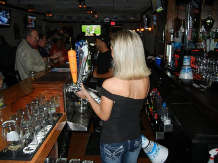 Bartendress serving behind the bar