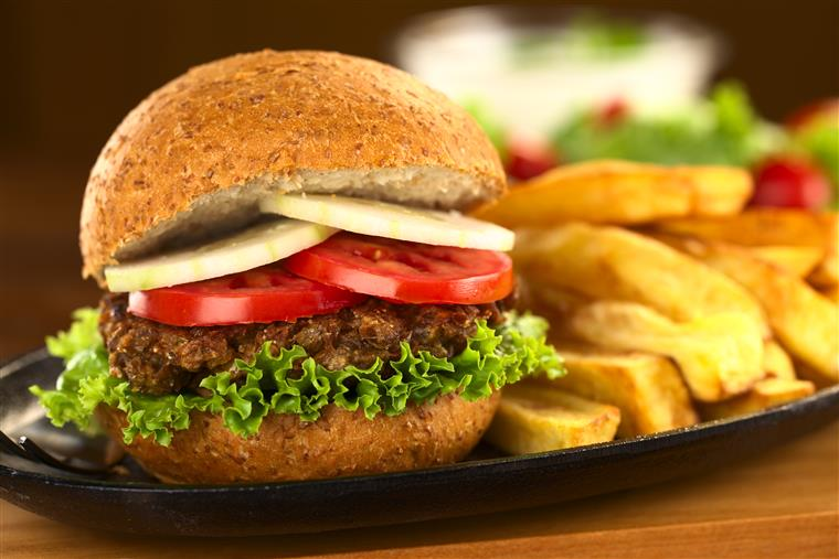 burger with lettuce, tomatoes and onions with a side of fries