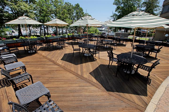 Outdoor patio with tables shaded by big umbrellas right by the waterfront