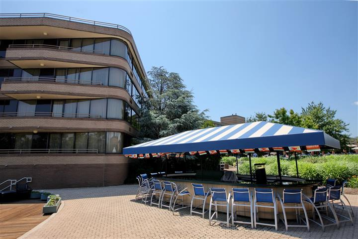 Outdoor bar shaded by a blue and white tent next to a building