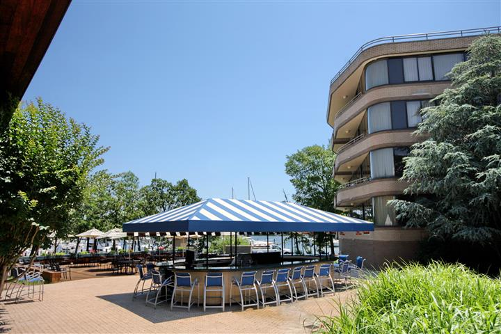 Outdoor bar shaded by a blue and white tent right by the patio
