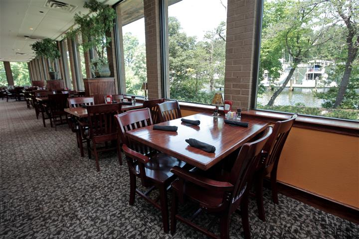 Tables set for a meal by the big windows overlooking big green trees