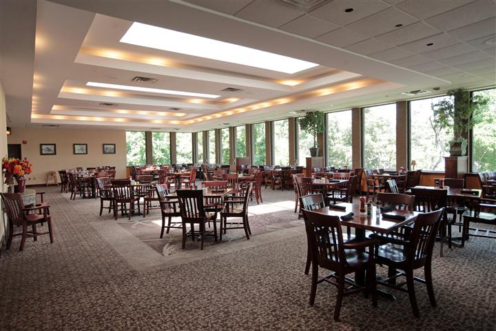 Restaurant hall with square tables all around and big windows facing green trees