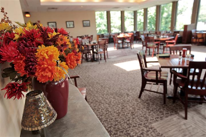 Vase with orange flowers decorating a counter top iin the restaurant hall