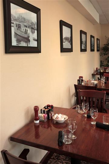 Tables set for a meal by the wall decorated with black and white photos