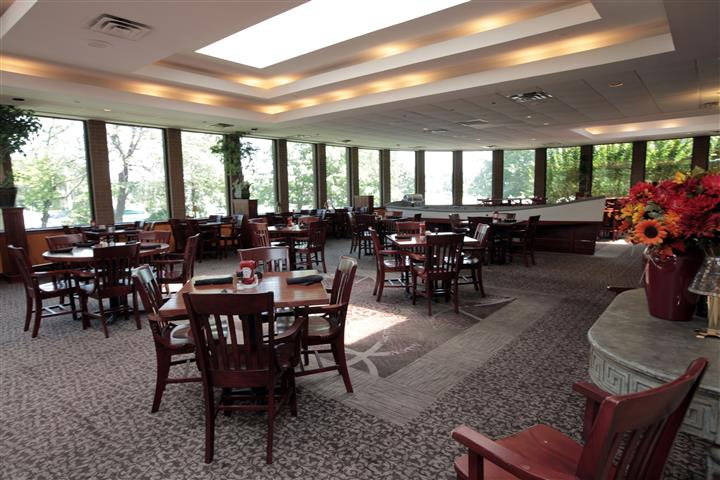 Restaurant hall with square tables all around and big windows facing trees