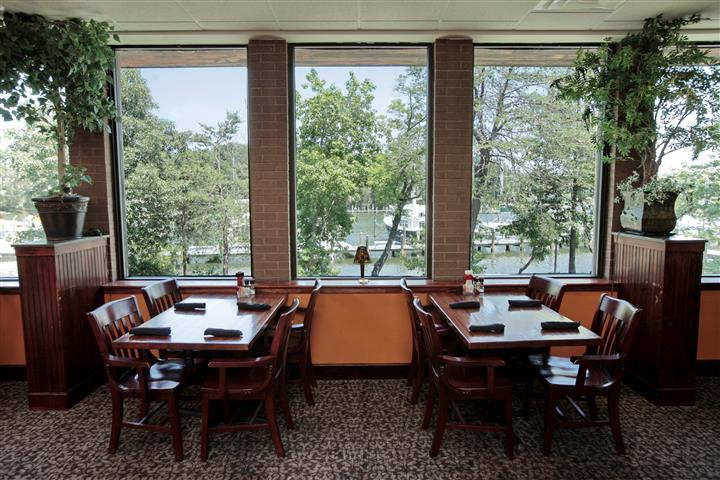 Tables set for a meal by the big windows overlooking big trees