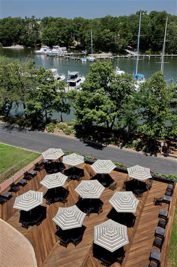 Photo shot from a height overlooking the patio with the big umbrellas and the green trees right by the water
