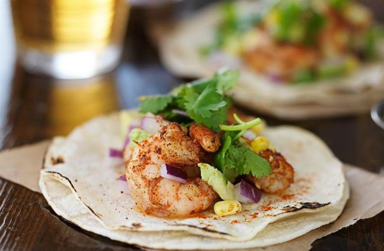 Shrimp tacos on table with glass of beer