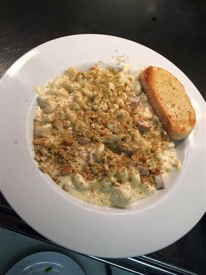 Mac and cheese with sausage and breadcrumbs with garlic bread on the side