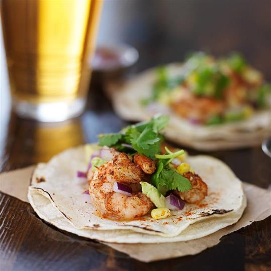 Shrimp tacos with cilantro, corn, and red onion