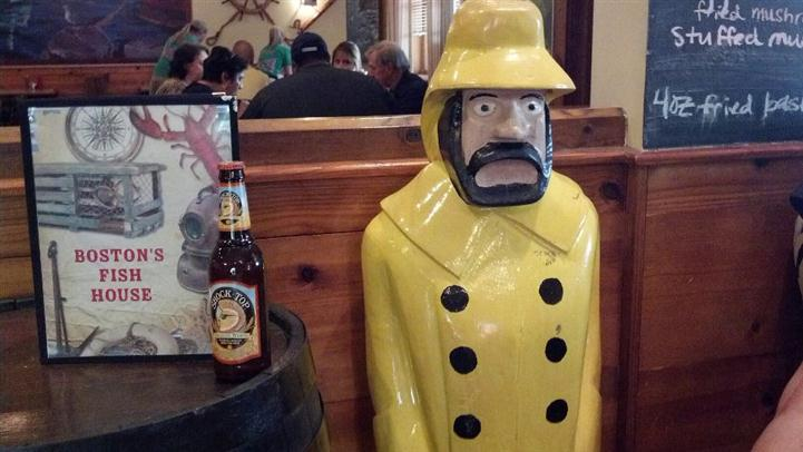 Sailor statue beside a beer bottle