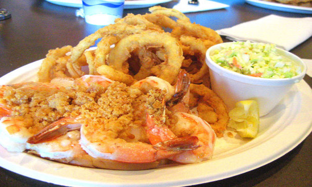 Fried shrimp with a side of onion rings and coleslaw