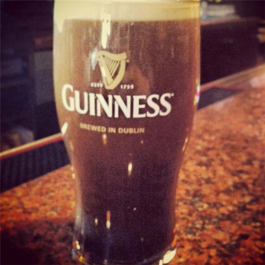 Guinness glass with a beverage inside of it