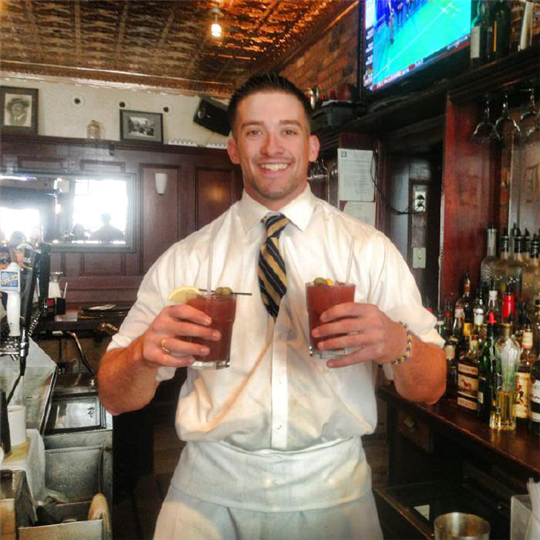Bartender smiling with 2 drinks in his hand