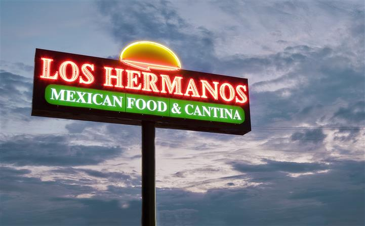 Outside lit up sign of Los Hermanos at night