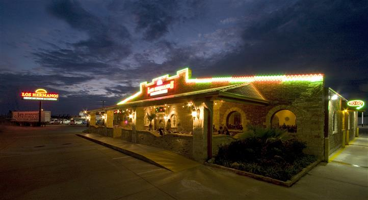 The outside of Los Hermanos lit up at night