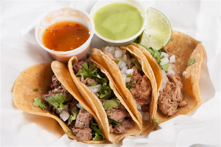 Four meat tacos sprinkled with cilantro and onion served with two sauces on a plate