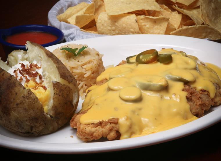 Fried chicken covered in queso with jalapenos slices on top. A baked potato with sour cream and cheese with a side of rice