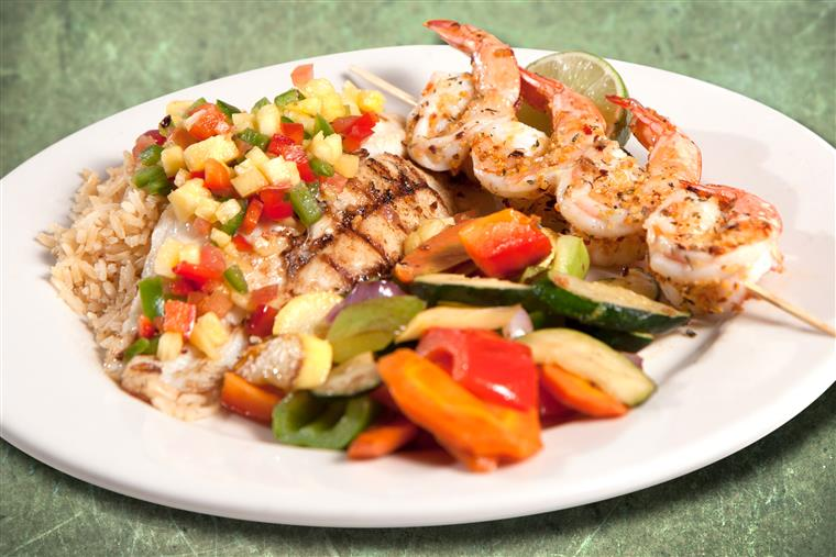 Shrimp skewer and grilled chicken served with rice topped with diced vegetables and a side of grilled vegetables