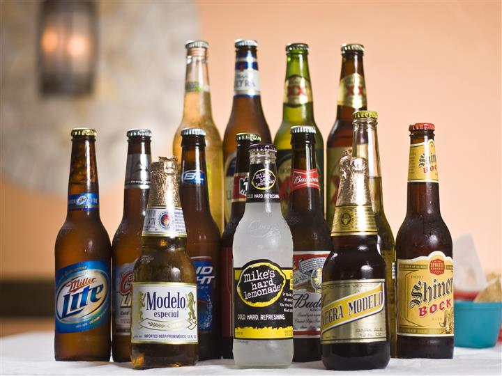 A countertop filled with different brands of bottled beers