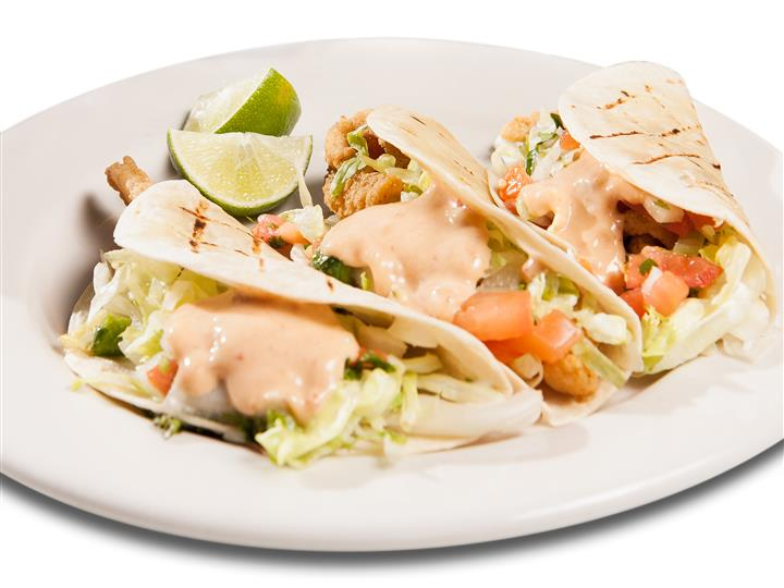 Grilled shrimp tacos covered in a creamy sauce