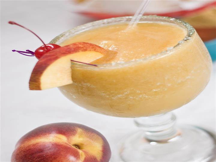 A frozen margarita with an apple wedge and a cherry on the rim of the glass