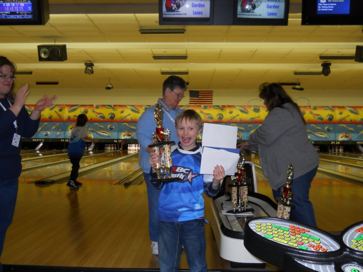Child holding trophy on bowling lane