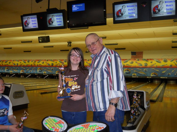 Man stands with a girl who's holding bowling trophy