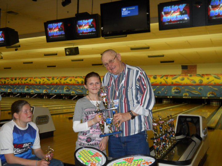 Man stands with a girl holding bowling trophy together