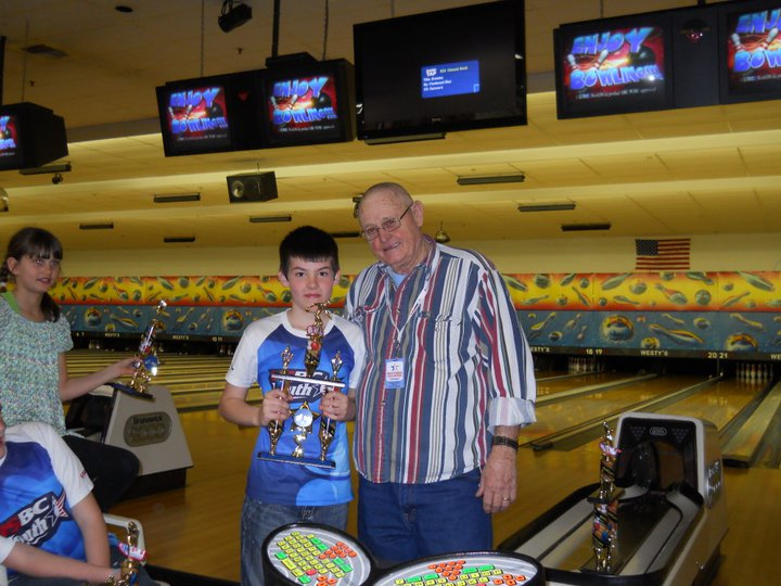 Man standing with boy who's holding bowling trophy