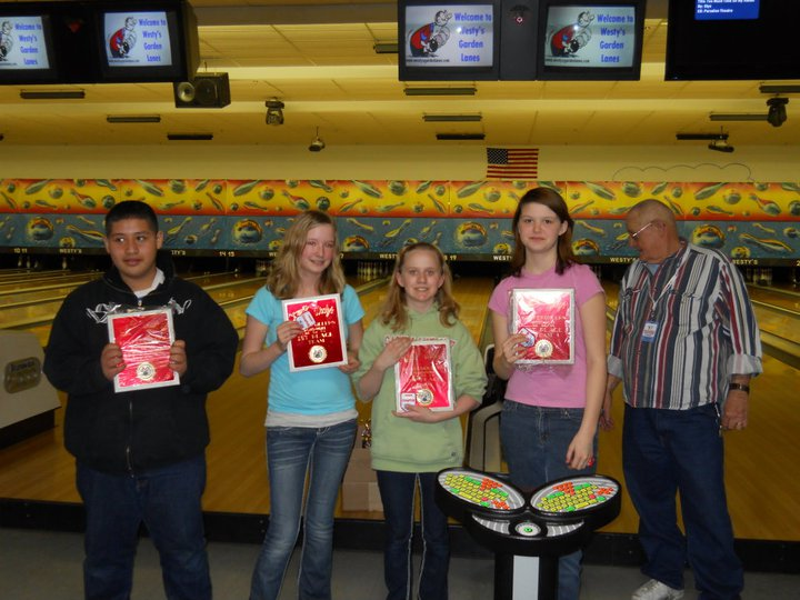 Male and female teenagers holding bowling awards