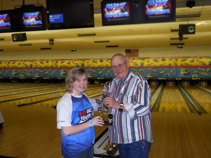 Man standing with young woman holding bowling trohy together