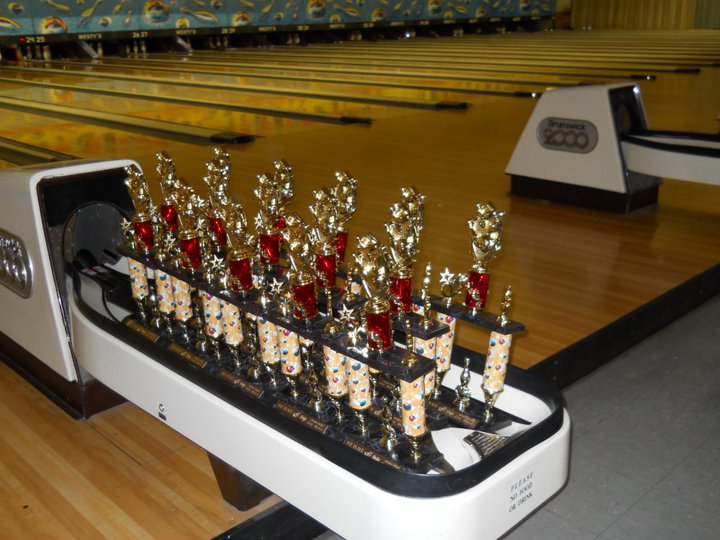 Westy's Garden Lanes bowling trophies set up on ball return machine