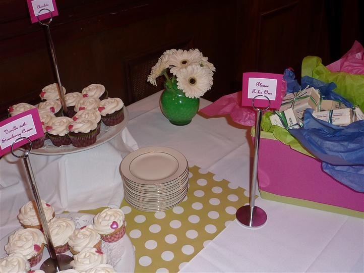 Plates stacked on a table with cupcakes
