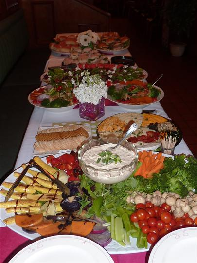 Catering table filled with vegetables, meats, and cheese