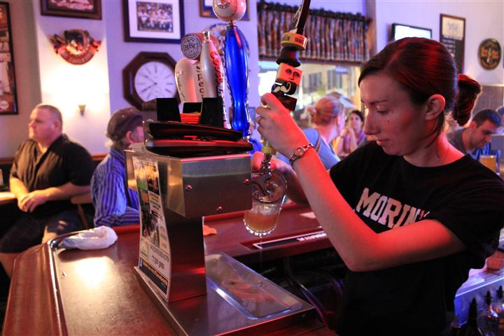 Bartender dispensing beer for a tap