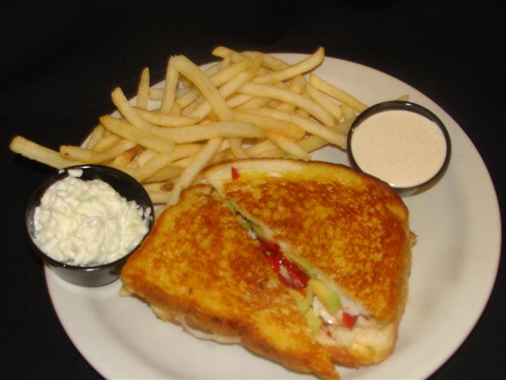 Sandwich grilled with side of fries and sauces