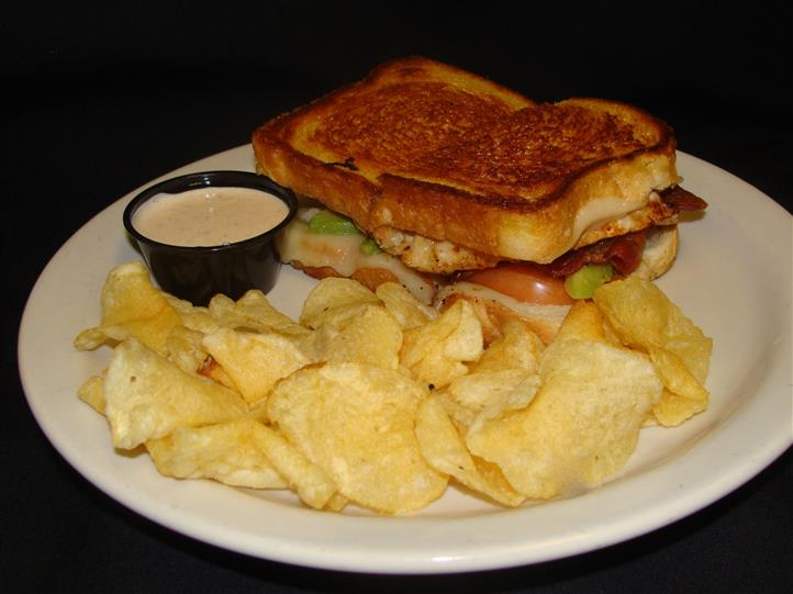 Grilled sandwich with side of potato chips and sauce
