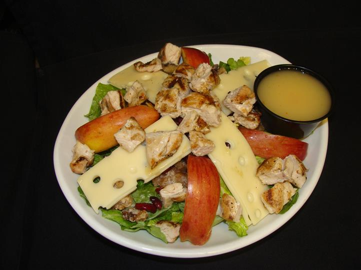 Salad topped with swiss cheese apples walnuts cranberries and sauce