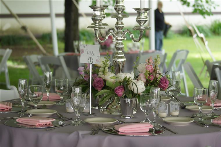 Table setup for a catering event with table clothes, flowers, elegant china and glassware.